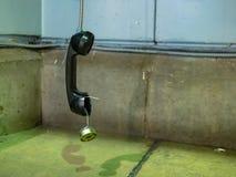 Broken payphone handset receiver hanging in a dark alleyway royalty free stock photography