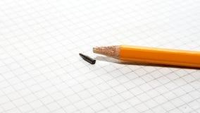 Broken pencil on checkered paper. Close up Stock Photos