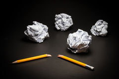Broken pencil, crumpled paper on black background. Stock Photo