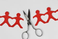 Broken people paper chain with scissors on white background - Br. Broken people paper chain with scissors on white background. Broken relationships concept royalty free stock photos