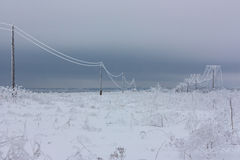 Broken phase electrical power lines with hoarfrost on the wooden electric poles on countryside in the winter after storm. Broken phase electrical power lines Stock Images