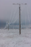 Broken phase electrical power lines with hoarfrost on the wooden electric poles on countryside in the winter after storm. Broken phase electrical power lines Stock Photo
