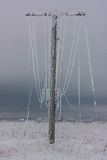 Broken phase electrical power lines with hoarfrost on the wooden electric poles on countryside in the winter after storm. Broken phase electrical power lines Stock Image