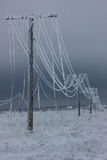 Broken phase electrical power lines with hoarfrost on the wooden electric poles on countryside in the winter after storm Royalty Free Stock Photo