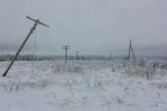 Broken phase electrical power lines with hoarfrost on the wooden electric poles on countryside in the winter after storm Royalty Free Stock Image