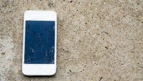 Broken phone on the concrete floor stock photo