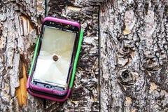 Broken phone, glass on tree trunk. Broken pink with green phone, glass on tree trunk nailed with rusty pins bark of tree crack hit background stock photography