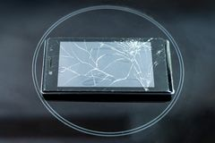 Broken phone rests on a black frosted glass, in the center of the circle. stock photos