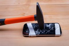 A broken phone on which stands a hammer on a wooden floor. Top view of a closeup stock images