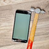 Broken phone screen. On a wooden floor with an old hammer royalty free stock photography