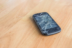 Broken phone on wood table. , damage phone with selective focus. Mobile phone malfunctioning, placed on a wooden table Royalty Free Stock Image