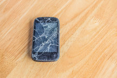Broken phone on wood table. , damage phone with selective focus. Mobile phone malfunctioning, placed on a wooden table Royalty Free Stock Photo
