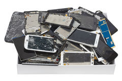Broken phones and tablets in the white cardboard box. Heap of the broken phones and tablets in the white cardboard box. Mass production devices are prepared for royalty free stock images