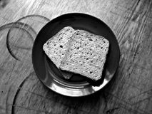 Broken pieces of bread on a plate on a old, shabby and scruffy kitchen wooden surface. Stock Images