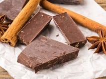 Broken pieces of chocolate, anise star, cinnamon sticks on parch Stock Photos