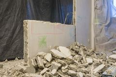 Broken pieces of wall lie near the wall being dismantled. Broken pieces of the wall lie near the wall being dismantled Stock Photography