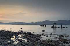 Broken Pier at Twilight. A broken pier at twilight with a mountain in the background Stock Photos