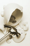 Broken piggy bank. Pieces of broken piggy bank with scattered coins and hammer Royalty Free Stock Photography