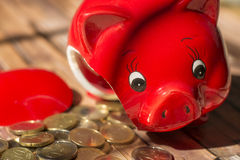 Broken piggy bank and coins Royalty Free Stock Photos