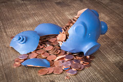 Broken piggy bank with coins scattered Royalty Free Stock Image
