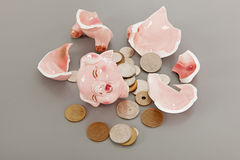 Broken piggy bank with coins Stock Image
