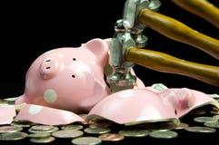 Broken Piggy Bank With Hammer. Blurred hammer hitting broken piggy bank with coins & cash Stock Photo