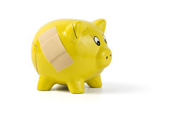 Broken piggy bank repaired with bandaid. Cracked yellow piggy bank repaired with bandaid, isolated on white stock images