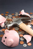 Broken piggy bank with savings money. Financial savings concept image featuring a piggy bank broken by a hammer loaded with money. Top copy space available Royalty Free Stock Image
