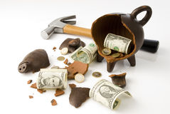 Broken piggy moneybox. A broken and empty clay piggy money box with money and hammer over white background Stock Photography