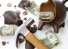 Broken piggy moneybox. A broken and empty clay piggy money box with money and hammer over white background Royalty Free Stock Photography