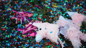 Broken pinata in the form of a horse lying on the grass. stock video