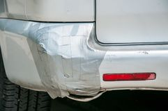 Broken plastic rear end bumper on the silver van glued with duct tape.  Royalty Free Stock Images