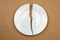 Broken plate on cardboard background Stock Image