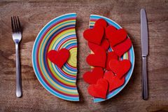 Broken plate with red hearts. Two pieces of broken colorful plate with one red heart on left side and many hearts on the right side on wooden background; symbol Royalty Free Stock Images