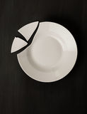 Broken plate. Broken white dish on black background. View from above. A concept Royalty Free Stock Images
