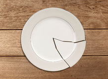 Broken plate on wood table Royalty Free Stock Photo