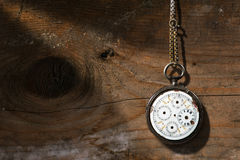 Broken Pocket Watch on Wooden Background. Old and vintage pocket watch with chain and without watch hands on a wooden background with copy space Royalty Free Stock Photos