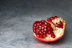 Broken pomegranate on scratched metall Stock Images