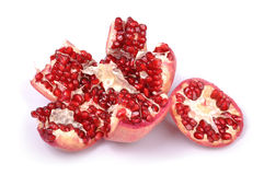 Broken pomegranate on white. Opened red juicy pomegranate on white background Royalty Free Stock Images