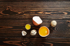 Broken quail & chicken eggs. On wood background Stock Images