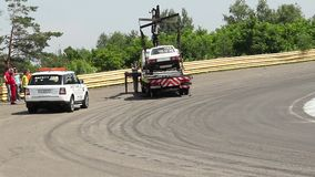 Broken racing car evacuated from track by truck, time-lapse. Stock footage stock footage