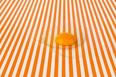 Broken raw egg on bright striped background, white and orange lines backdrop, close up top view stock photo