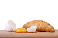 Broken raw egg on a cutting board with fresh pastries Stock Photo