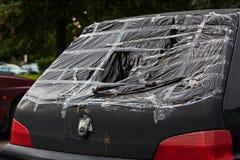 Broken rear window. A closeup of a broken rear window of a small black car Stock Image