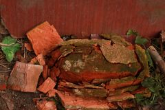 A broken red brick licks the ground. Among the grass stock images