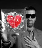 Broken red glass heart businessman metaphor. Black background studio shot Royalty Free Stock Photo