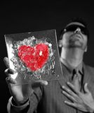 Broken red glass heart businessman metaphor. Black background studio shot Royalty Free Stock Image