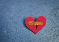 Broken red heart. With a bandaid, on blue Royalty Free Stock Images