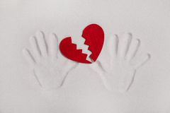 Broken red heart with hand prints in the sand for love sickness Royalty Free Stock Photo