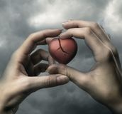 Broken red heart in hands Royalty Free Stock Photo